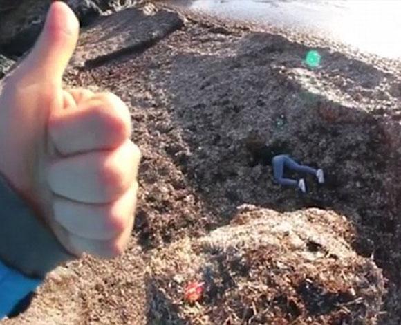 فتاة تقع قبالة صخرة على شاطئ البحر
